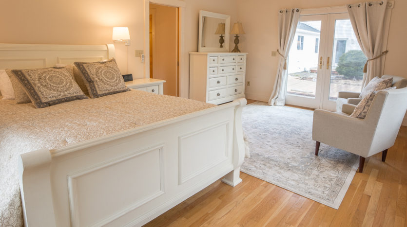 Master queen bedroom with sitting area and french doors to deck